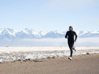 Man Jogging on Dirt Road in Winter