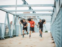 Men Running Exercising on Bridge with Medicine Balls