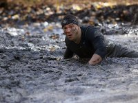 Man Crawling Through Mud In Tough Mudder Race