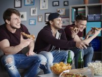 Men Watching TV Eating Pizza on Couch