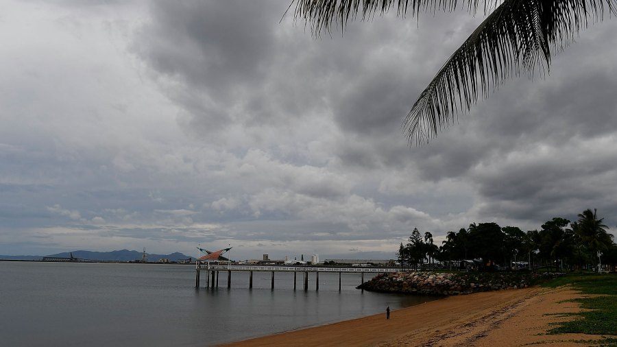 Grey clouds over one of the Strand beaches with its jetty as residents prepare for Cyclone Debbie in  Australia.