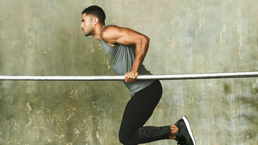 Fit man doing bodyweight dips on parallel bars