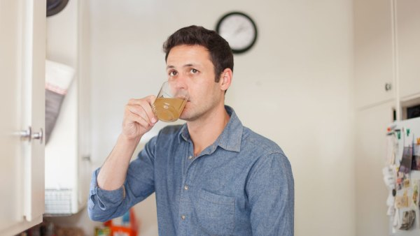 Man drinking apple cider vinegar beverage