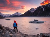 Adventurer at Tasman Glacier Lake and Mount Cook during colorful sunrise.
