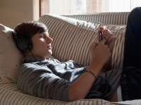 Boy texting on couch