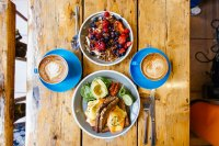 Breakfast spread with yogurt and granola and poached eggs over salmon