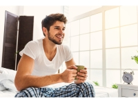 Man Drinks Cup Of Coffee In Bed After Waking Up Early