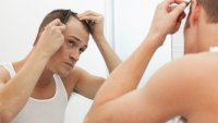 Man combing hair looking in mirror