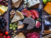 Cheese board with charcuterie, nuts, and fruit