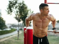 Fit man performing wide-grip dips for chest