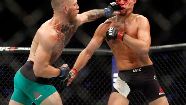 Conor McGregor hits Nate Diaz with a left during their welterweight rematch at the UFC 202.
