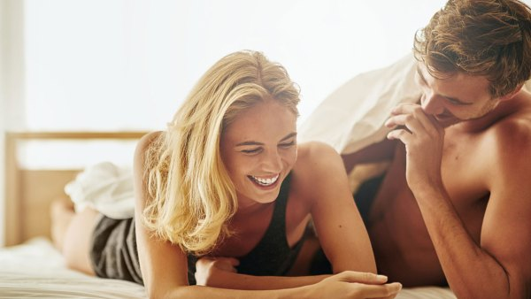 Young couple laughing on bed