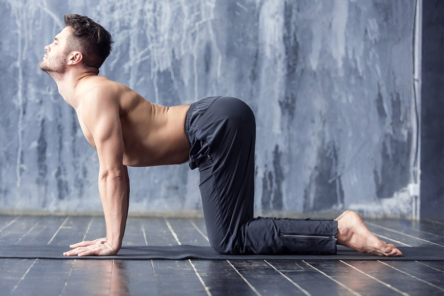 Man does cow yoga pose