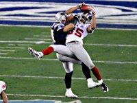 David Tyree of the New York Giants catches a pass for a first down against the New England Patriots in the fourth quarter of Super Bowl 42