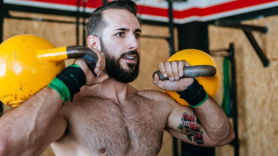 Man working out with two kettlebells