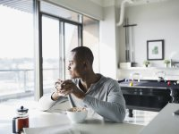 Man eating breakfast at home