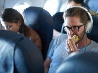 Man eating sandwich on airplane