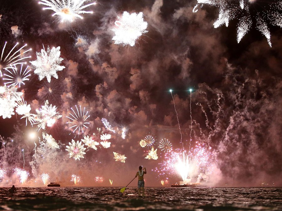 Man paddle boarding with fireworks in sky