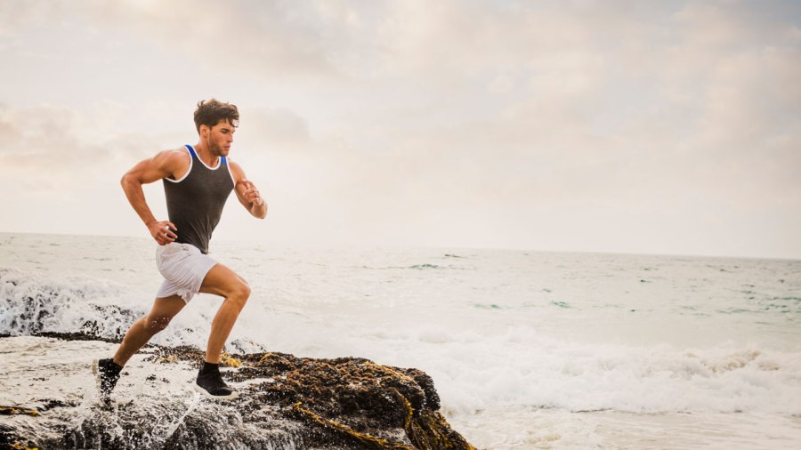 Young, fit man running on beach