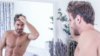 Man checking out hair in mirror