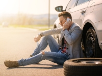 A Young Man With A Silver Car That Broke Down On The Road.
