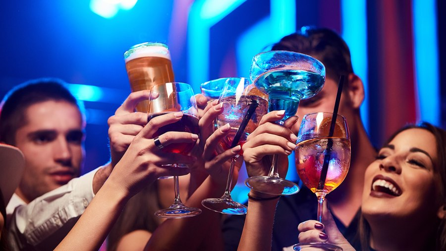 Group of young people toasting at a night club or bar