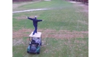 Watch: Dude Crushes Amazing Golf Shot From the Top of a Moving Cart