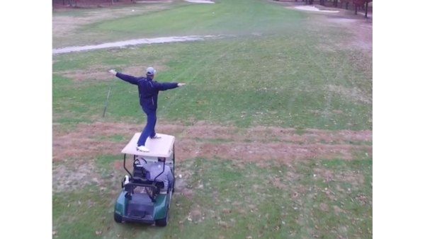 Dude crushes golf shot from top of a moving cart