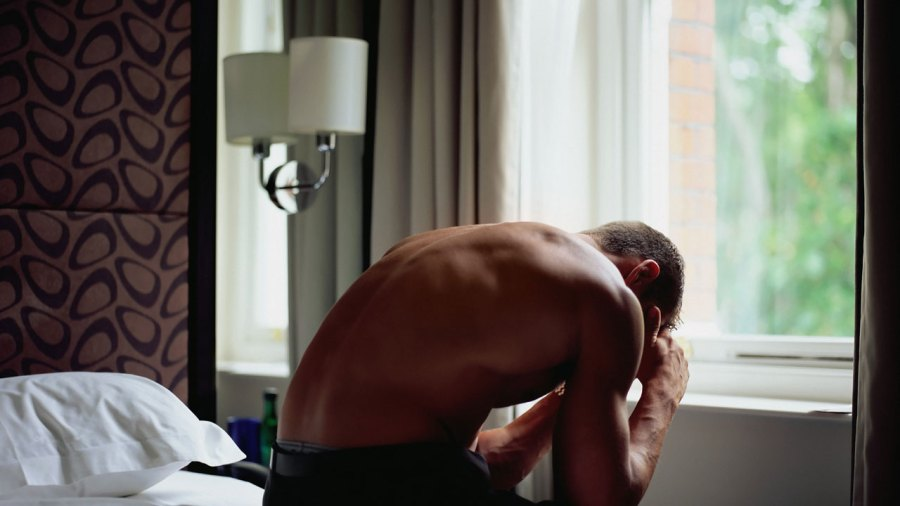 Man sitting on bed with migraine