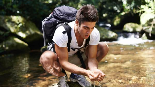 Hiker drinking from river