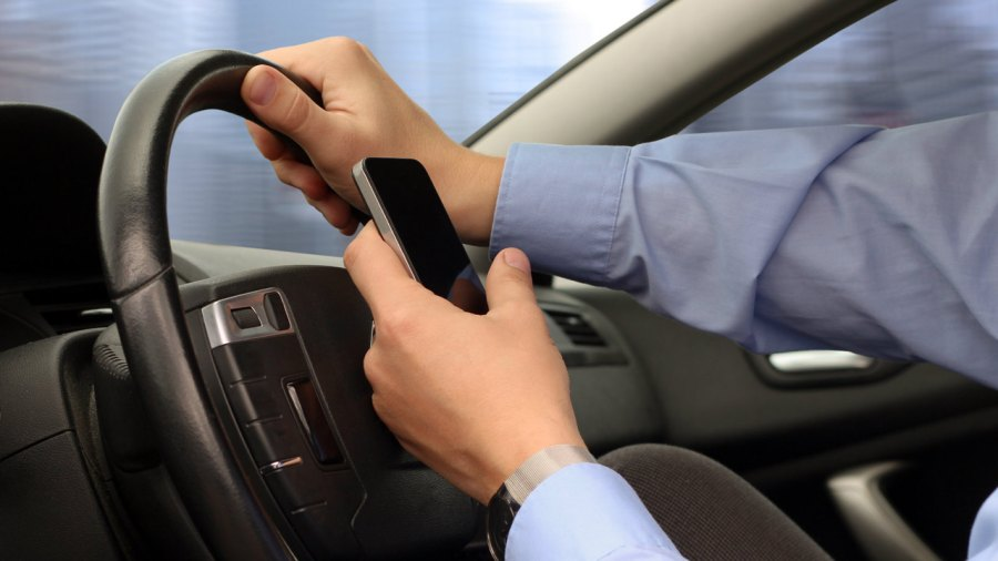 Man Holding Cell Phone While Driving Car