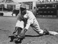 Jackie Robinson catching a ground ball in stadium