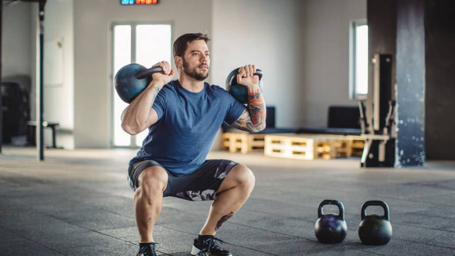Man doing double kettlebell front squat
