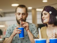 Man Drinking Cup of Soda With Woman