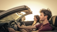 Couple Drive A Car On The Highway During A Sunset