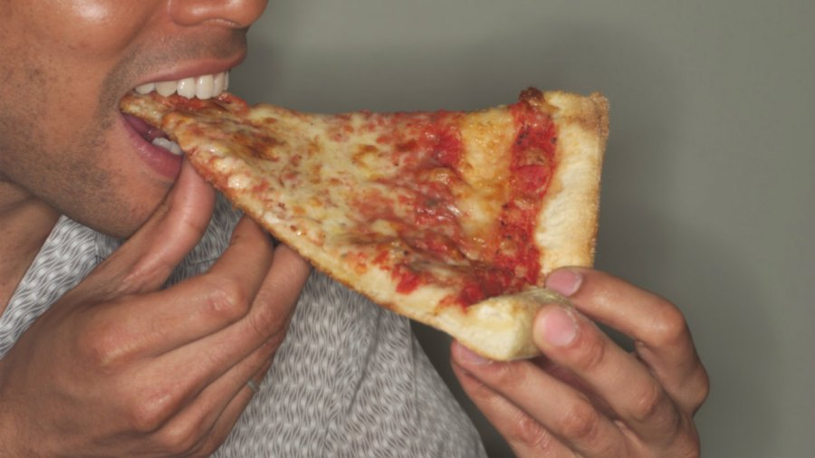 Man Eating Slice of Pizza