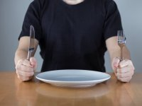 Man seated with knife and fork and empty plate