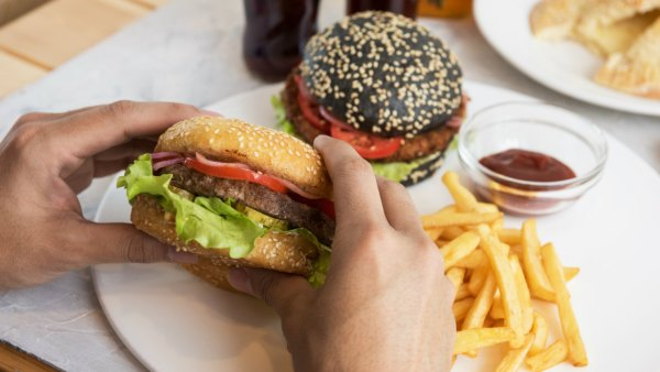 Man Holding Hamburger with Side Of Fries