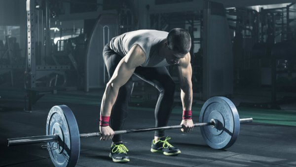 Man lifting barbell at gym