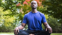 Man Relaxing In Park Doing Yoga Meditation