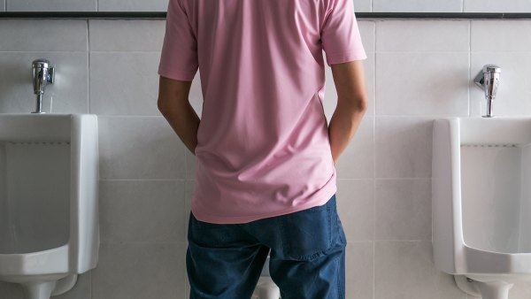 Man standing to pee at a urinal