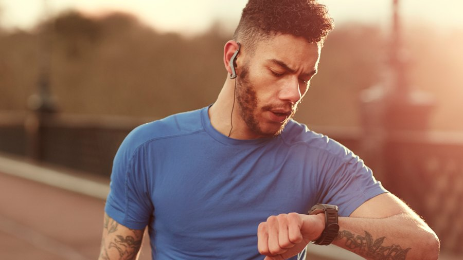 Man Checks Fitness Tracker During Workout