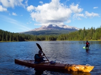 Mt Hood, Is Seen Behind A Cloud In As A Canoer Navigates Trillium Lake.