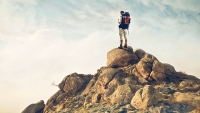 Fit Guy With A Travel Backpack Stands On Top Of A Boulder
