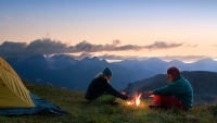 Couple Camping And Sitting Around A Fire In The Mountains