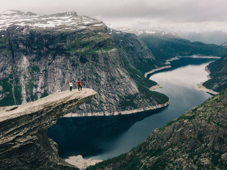 Two young adults standing on the Trolltunga in Norway