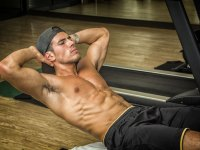 Muscular guy doing crunches in gym