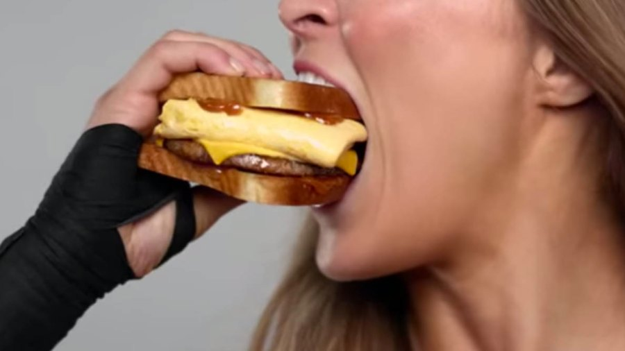 Ronda Rousey takes a bite out of the new Carl's Jr. Cinnamon Swirl French Toast Breakfast Sandwich.