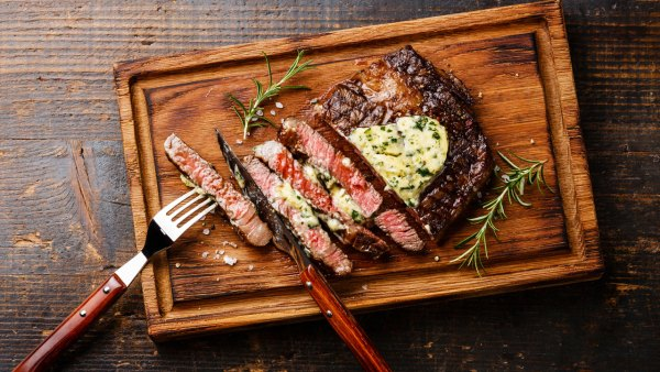 Sliced grilled steak Ribeye with herb butter on cutting board