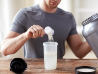 Man Adding Scoop Of Protein